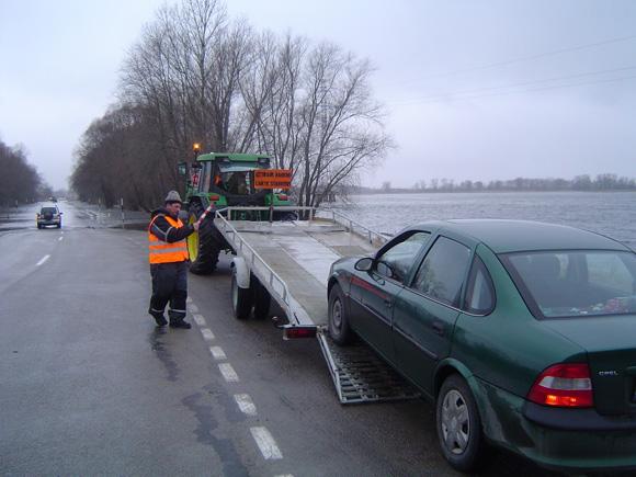 Nuo 15 val. lengvosios mašinos vėl gabenamos apsemtu kelio į Rusnę ruožu. (O. Lidžiaus nuotr.)